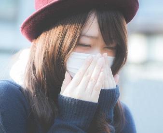 咳が出るのでマスクをする女性